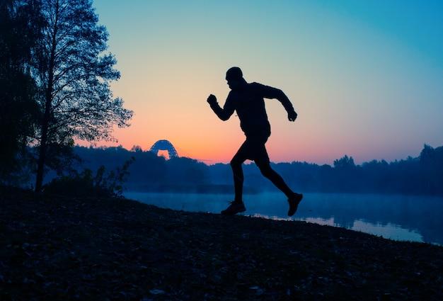 Zdjęcie biegnącego sportowca o zachodzie słońca