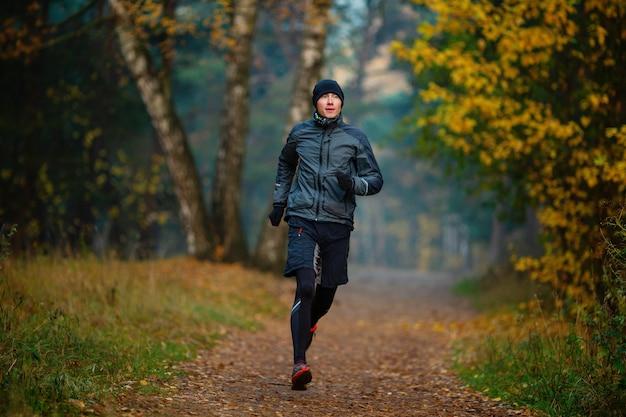 Zdjęcie biegnącego sportowca w jesiennym parku