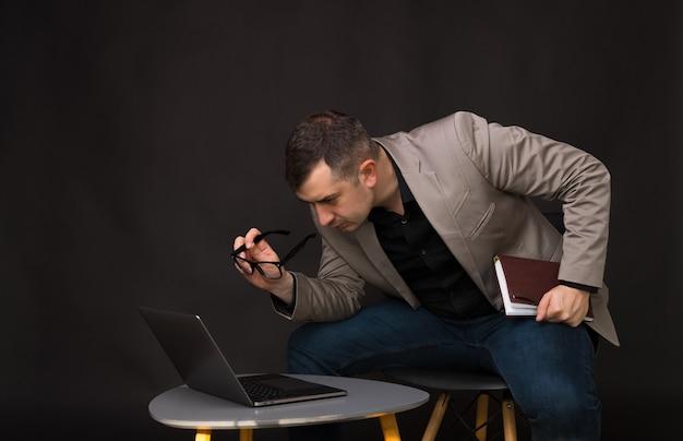 Zdjęcie biznesmen, zmartwiony patrząc przez okulary na problem problemu, na ciemnym tle