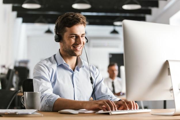 Zdjęcie biznesowego mężczyzny w wieku 20 lat, noszącego ubrania biurowe i słuchawki, pracującego na komputerze w centrum obsługi telefonicznej