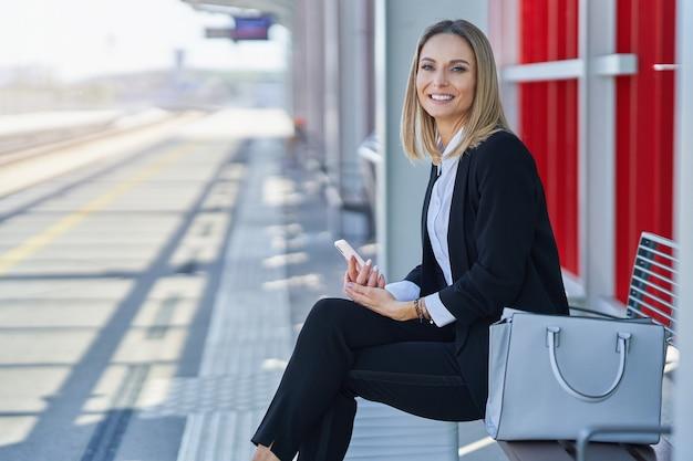 Zdjęcie bizneswoman siedzącej i czekającej na stacji kolejowej