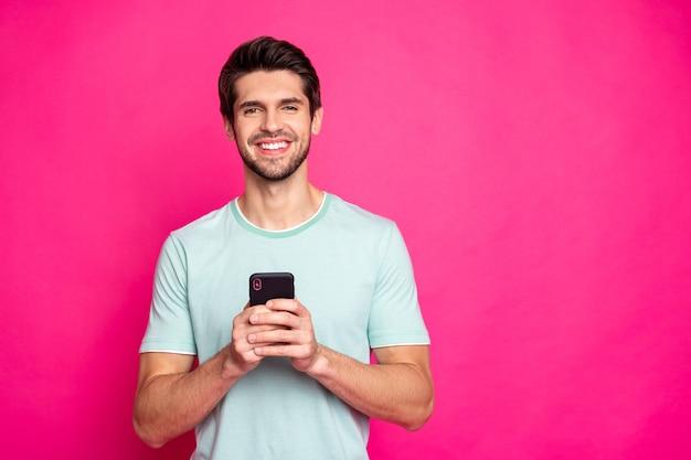 Zdjęcie blogera facet trzymający telefon w rękach sprawdzanie abonentów toothy uśmiechnięty nosić strój na co dzień na białym tle żywy różowy kolor tła