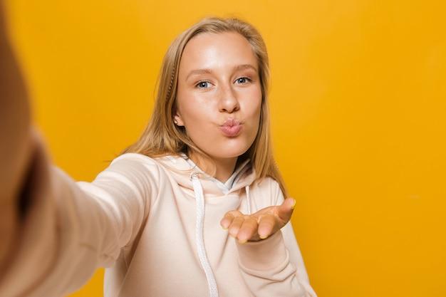 Zdjęcie blond kobiety 16-18 lat z aparatami ortodontycznymi uśmiecha się i robi selfie, odizolowane na żółtym tle