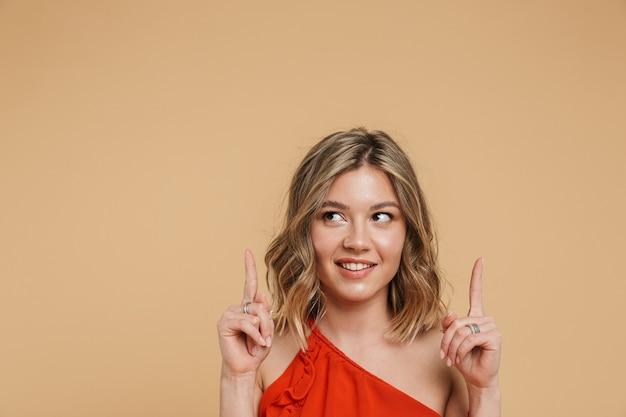 Zdjęcie blond ślicznej kobiety w wieku 20 lat w czerwonej sukience, wskazując palcami w górę na copyspace i patrząc na bok na białym tle nad beżową ścianą