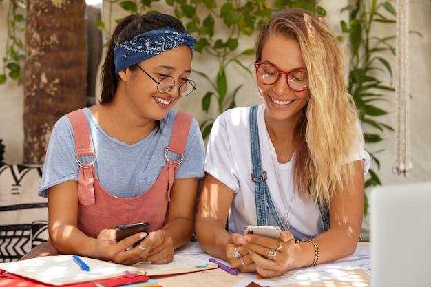 Zdjęcie blondynki siedzącej obok jej azjatyckiej przyjaciółki