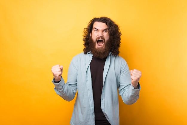 Zdjęcie brodatego hipstera świętującego i krzyczącego na żółtym tle