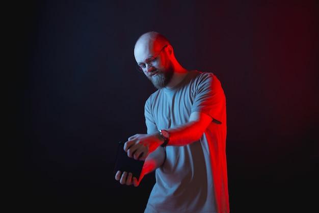 Zdjęcie brodatego mężczyzny hipster grając w gry na tablecie na niebieskie i czerwone neony
