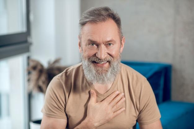 Zdjęcie brodatego mężczyzny kładącego rękę na sercu