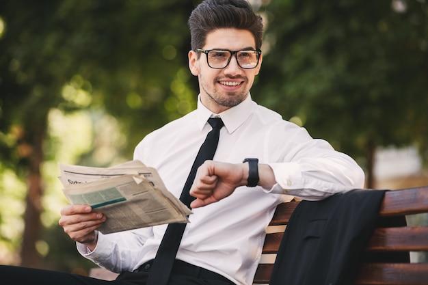 Zdjęcie brodatego mężczyzny w garniturze czytającego gazetę na ławce w zielonym parku i patrząc na zegarek