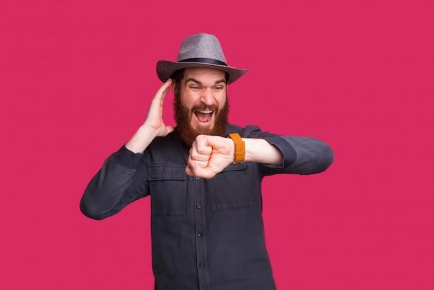 Zdjęcie brodatego mężczyzny w kapeluszu, krzyczącego i patrzącego na zegarek, opóźnione na spotkaniu