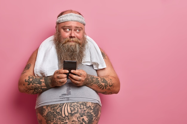 Zdjęcie brodatego mężczyzny z nadwagą czyta sms na smartfonie, zajęty fitnessem w domu, sprawdza wyniki w aplikacji sportowej, ile spalił kalorii, ma wytatuowany brzuch wystający z niewymiarowej koszulki