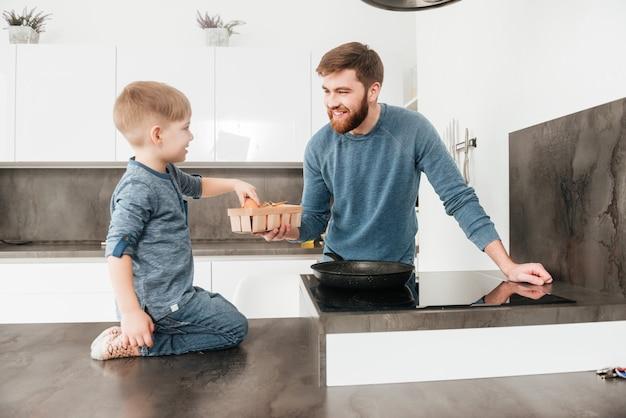 Zdjęcie brodatego ojca ubranego w niebieski sweter gotującego w kuchni ze swoim małym słodkim synkiem