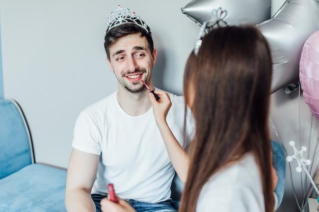 Zdjęcie brunetki córki robi makijaż pędzlem do ojca