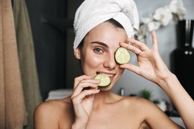Zdjęcie brunetki kobiety z ręcznikiem na głowie trzymając plasterki ogórka na jej twarzy