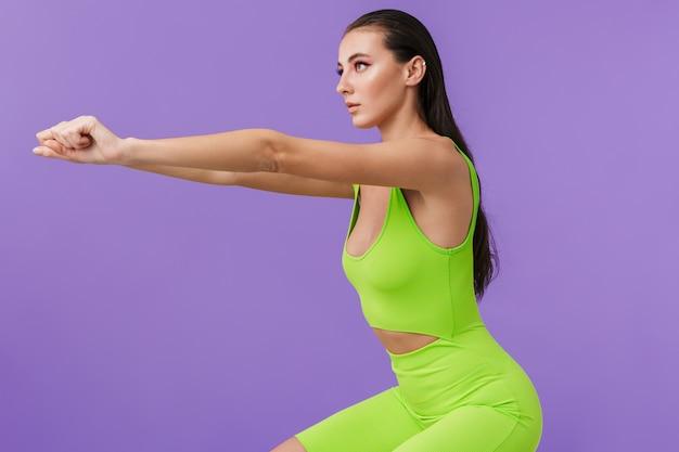 Zdjęcie brunetki moda kobieta ubrana w chudy kombinezon robi ćwiczenia i nie może się doczekać