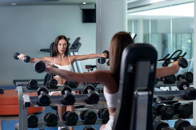 Zdjęcie brunetki ubranej w biały top z siatki, białe sportowe spodenki na siłowni wykonujące ćwiczenie, siedząc na krześle z hantlami z założonymi na boki ramionami.