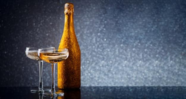 Zdjęcie butelki wina w złotym opakowaniu z dwoma kieliszkami do wina na szarym tle