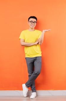 Zdjęcie całego ciała azjaty w żółtej koszuli na pomarańczowej ścianie
