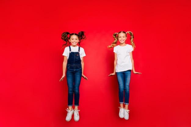 Zdjęcie całego ciała dwóch pozytywnych małych dziewczyn skaczących cieszyć się wiosennymi weekendami czas wolny nosić białą koszulkę dżinsowe dżinsy kombinezony trampki izolowane czerwony kolor tło