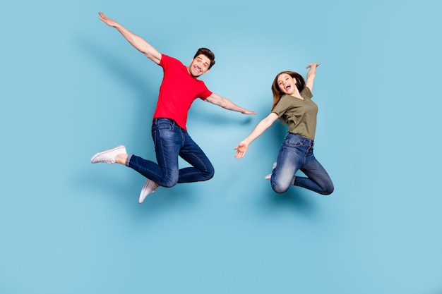 Zdjęcie całego ciała dwóch romantycznych małżonków, którzy skaczą, trzymają się za ręce jak skrzydła samolotu, czuć się szczerym w codziennych stylowych ubraniach odizolowanych na niebieskim tle