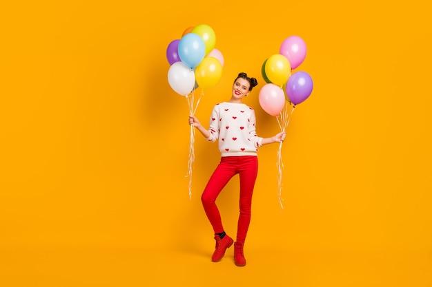 Zdjęcie całego ciała ładnej pani przyniesie wiele kolorowych balonów na imprezę niespodziankę dla przyjaciół na imprezę nosić sweter w serduszka