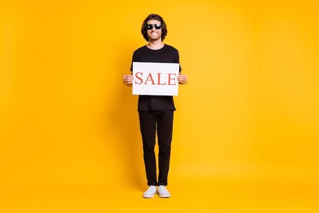 Zdjęcie całego ciała młodego człowieka stoisko przytrzymaj afisz sprzedaż nosić czarny t-shirt spodnie białe trampki okulary przeciwsłoneczne na białym tle żółty kolor tła