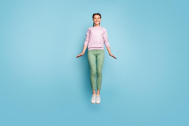 Zdjęcie całego ciała pięknej kobiety skaczącej wysoko w górę ciesz się niesamowitą pogodą w słoneczny wiosenny dzień radując się dobrym nastrojem nosić swobodny różowy sweter zielone spodnie izolowane niebieski kolor