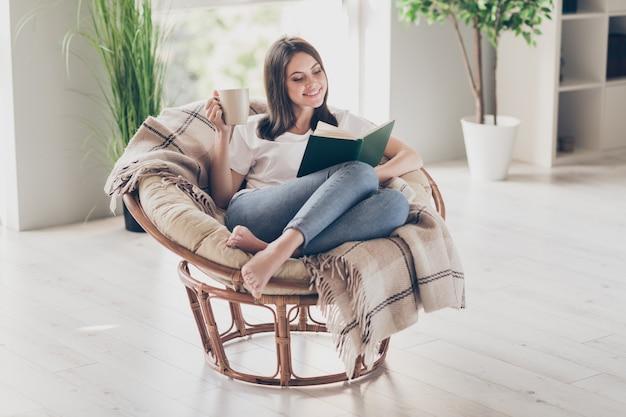 Zdjęcie całego ciała pozytywnej młodej dziewczyny siedzieć wiklinowym fotelu czytać książki trzymać filiżankę kawy nosić białą koszulkę bosą stopą w domu w pomieszczeniu