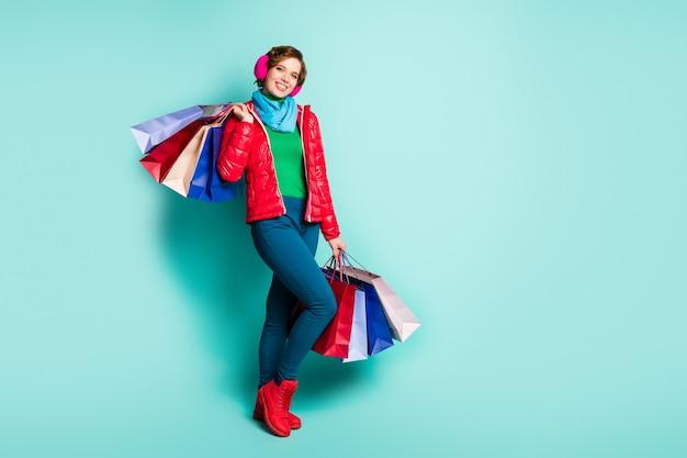Zdjęcie całego ciała pozytywnej turystki trzyma wiele toreb, które kupuje jesienią jesień na weekend zielony sweter czerwony sezon nosić buty różowe niebieskie spodnie spodnie izolowane turkusowy kolor ściana