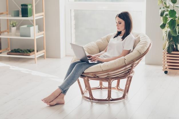 Zdjęcie całego ciała skupionej kobiety siedzącej wiklinowym krześle, pracującej na laptopie, noszącej ubrania w stylu casual w domu w domu