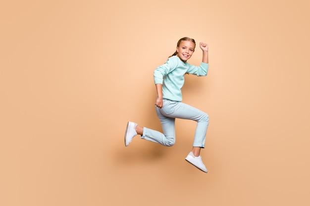 Zdjęcie całego ciała ślicznej dziewczynki w swobodnym ubraniu biegnącej wysoko, skacząc wysoko na tle pastelowej beżowej ściany