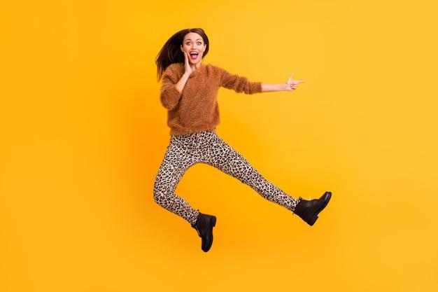 Zdjęcie całego ciała śmiesznej pani skaczącej wysoko, wskazując palcem puste miejsce, doradzając niskie ceny w ostatnim sezonie
