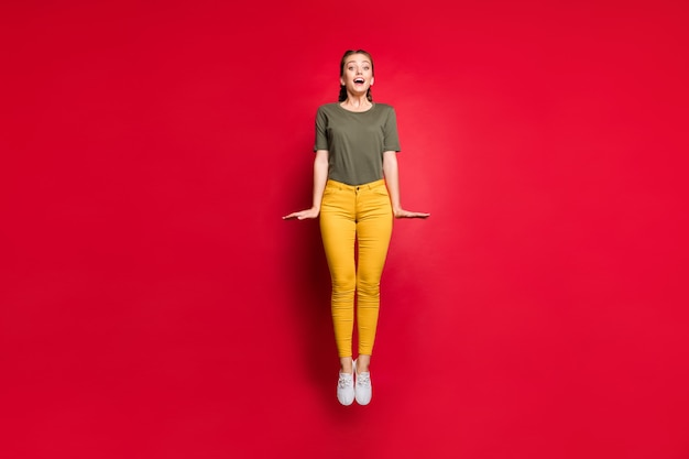 Zdjęcie całego ciała szalonej młodej damy skaczącej wysoko, spędzającej najlepszy wolny czas podekscytowany wesoły nastrój ubranie na co dzień żółte spodnie zielona koszulka na białym tle czerwony kolor tło
