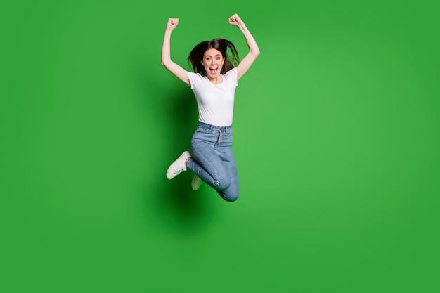 Zdjęcie całego ciała zachwyconej dziewczyny, która podskakuje, podnosi pięści, nosi białe ubrania w stylu casual, odizolowane na zielonym tle