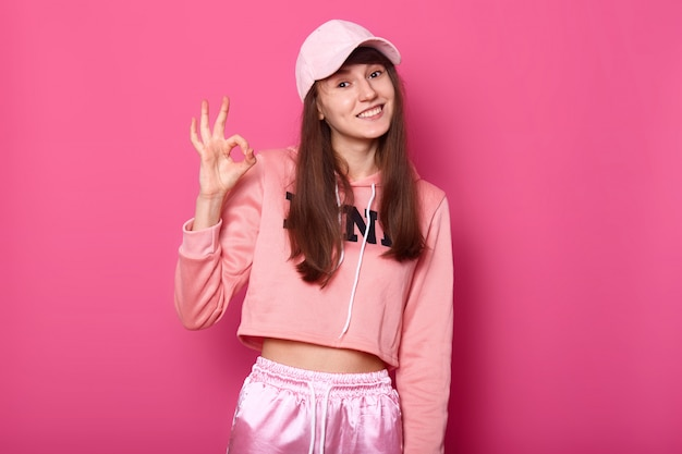 Zdjęcie całkiem atrakcyjnej damy w różowym swetrze sportowym, dresach, czapce, pokazuje znak porządku