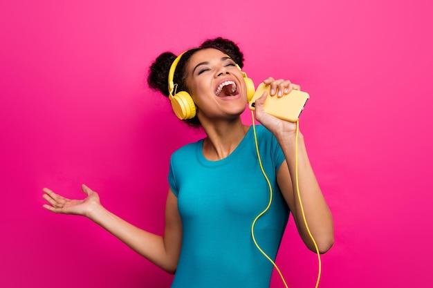 Zdjęcie całkiem funky ciemnej skóry pani trzymaj telefon słuchaj muzyki śpiewają nowoczesne słuchawki