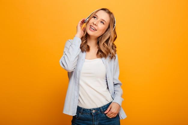 Zdjęcie całkiem kaukaskiej kobiety noszącej aparaty ortodontyczne w swobodnej odzieży korzystającej z muzyki za pośrednictwem nowoczesnych słuchawek, odizolowane na żółtej przestrzeni
