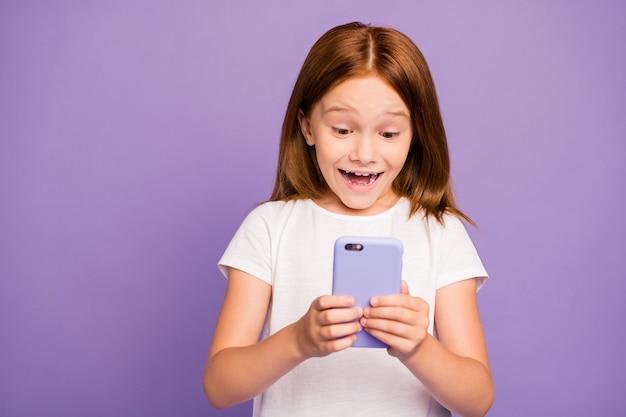 Zdjęcie całkiem mała dziewczyna imbir trzymając telefon marzycielskiej twarzy