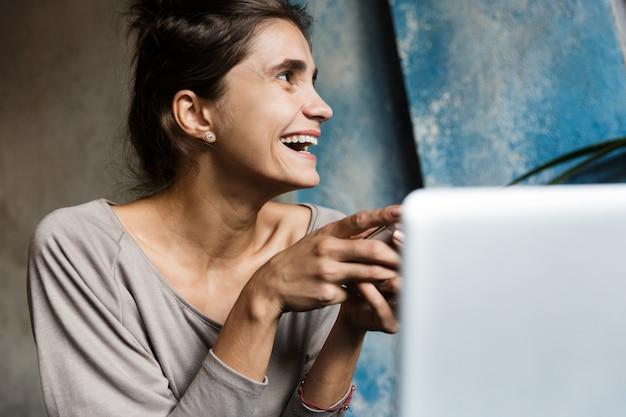 Zdjęcie całkiem młoda kobieta siedzi w pomieszczeniu kawiarni przy użyciu komputera przenośnego i telefonu komórkowego.