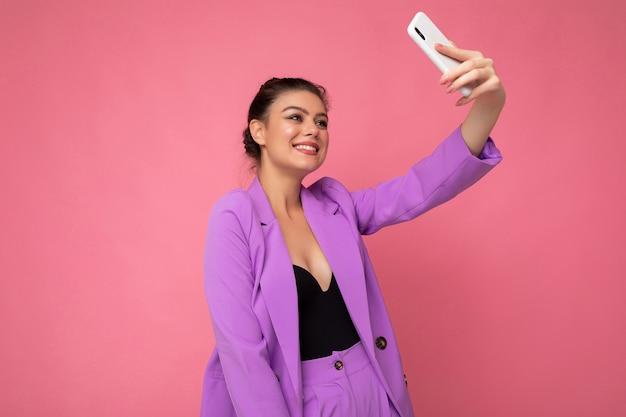 Zdjęcie całkiem młoda kobieta ubrana w fioletowy garnitur biorąc zdjęcie selfie
