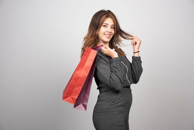 Zdjęcie całkiem młodej kobiety pozuje z torbami na zakupy.