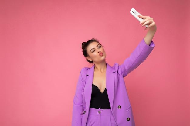 Zdjęcie całkiem młodej kobiety w fioletowym garniturze, robiącej zdjęcie selfie na telefonie komórkowym na białym tle