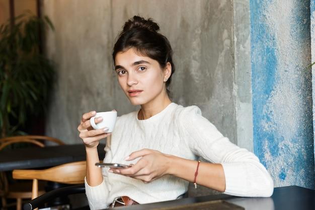Zdjęcie całkiem poważne młoda kobieta siedzi w kawiarni picia kawy w pomieszczeniu za pomocą telefonu komórkowego na czacie.