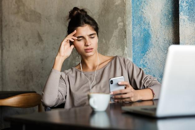 Zdjęcie całkiem poważne młoda kobieta siedzi w kawiarni w pomieszczeniu przy użyciu komputera przenośnego i telefonu komórkowego.