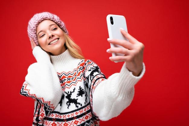 Zdjęcie całkiem pozytywne młoda blondynka sobie ciepłą czapkę z dzianiny i zimowy ciepły sweter stojący na białym tle nad czerwonym tle przy użyciu telefonu komórkowego biorąc selfie zdjęcie patrząc na wyświetlacz urządzenia.