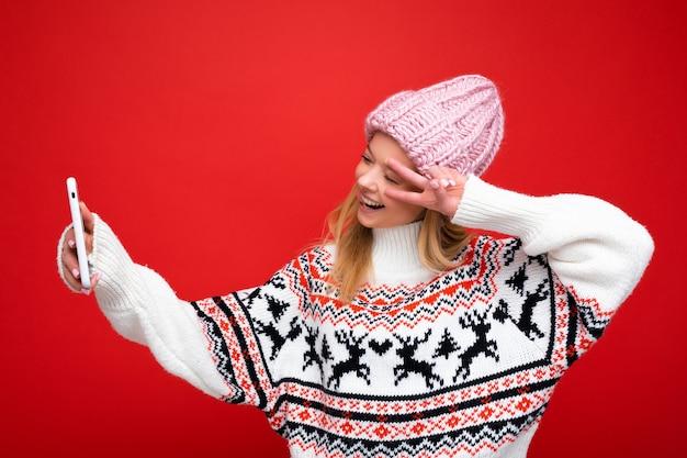 Zdjęcie całkiem pozytywnej młodej kobiety blondynka na sobie ciepłą czapkę i zimowy ciepły sweter