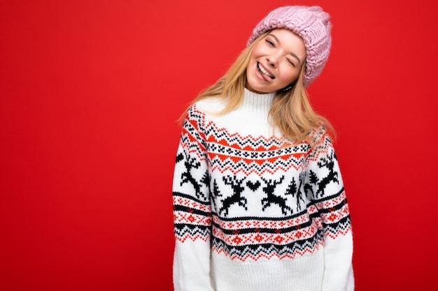 Zdjęcie całkiem pozytywny szczęśliwy, radosny, młoda blond osoba płci żeńskiej na białym tle na czerwonym tle