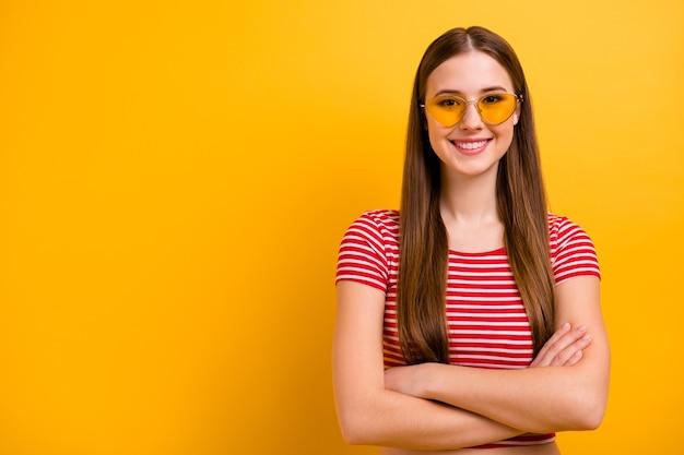 Zdjęcie całkiem urocza pewna siebie młoda dziewczyna założonymi rękami uśmiechnięty trener przywództwa gotowy rozpocząć szkolenie pusta przestrzeń nosić okulary przeciwsłoneczne w paski biała czerwona koszula jasnożółty kolor tła