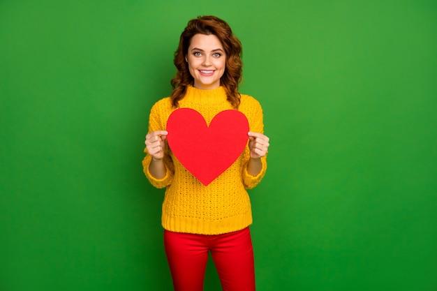 Zdjęcie całkiem uroczej falistej pani trzymaj papierową pocztówkę w kształcie serca zaprosić chłopaka kochanka romans randkowy nosić żółty sweter z dzianiny czerwone spodnie na białym tle jasnozielony kolor ściana