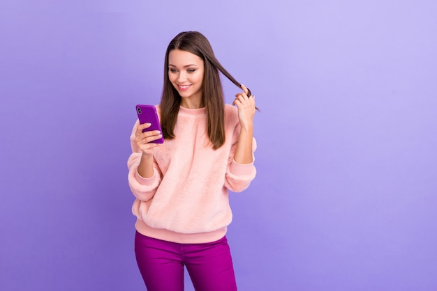Zdjęcie całkiem uzależnionej blogerki trzymającej telefon, bawiącej się lokami na fioletowej ścianie